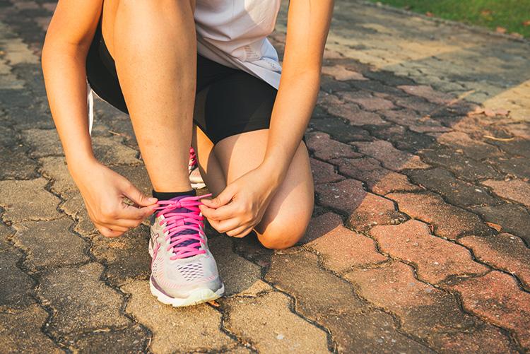 ragazza triathlon che si allaccia le scarpe prima di correre 2019