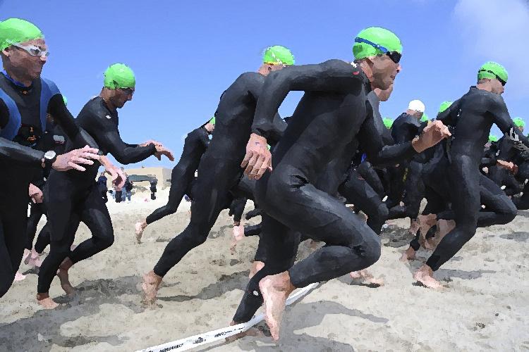 Triatleti si tuffano in acqua all'inizio di una gara