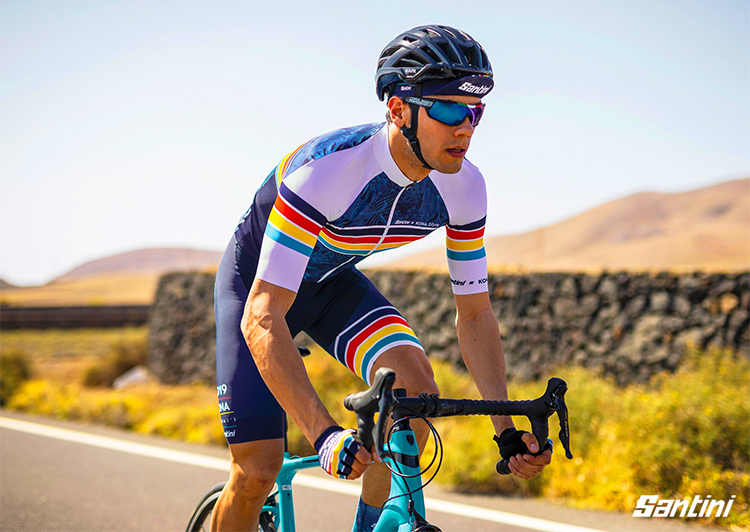 Un triatleta in sella a una bici vestito con i capi Santini X IRONMAN