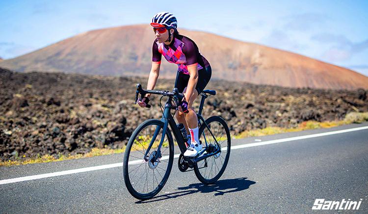 Una triatleta donna pedala vestita con abbigliamento Santini X IRONMAN