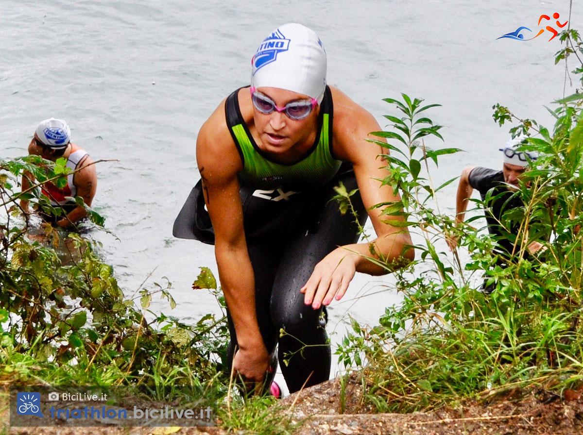 All'uscita dalla frazione a nuoto una concorrente si sfila come da regolamento la muta