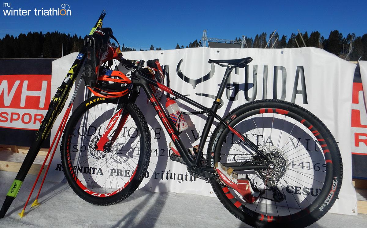 L'attrezzatura completa per una gara winter triathlon: bike, scarpe, casco, sci da fondo e bastoncini.