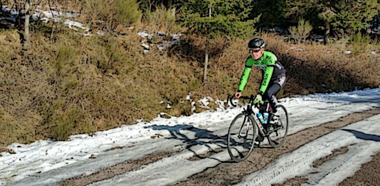 Ciclista pedala in sella a bici su strada con neve