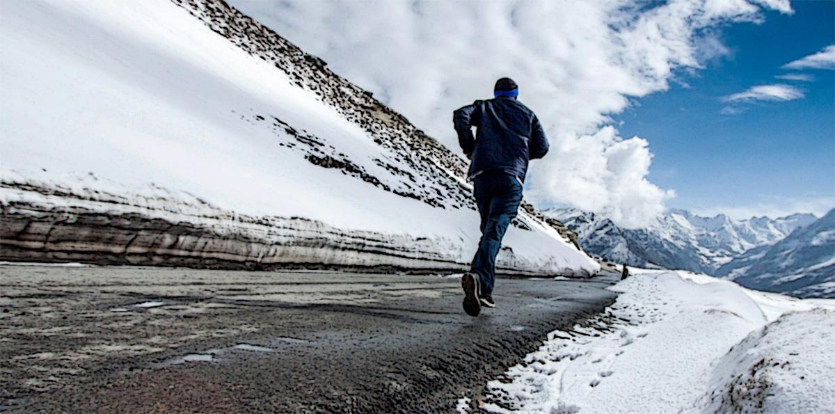 Runner che corre su una strada circondato dalla neve