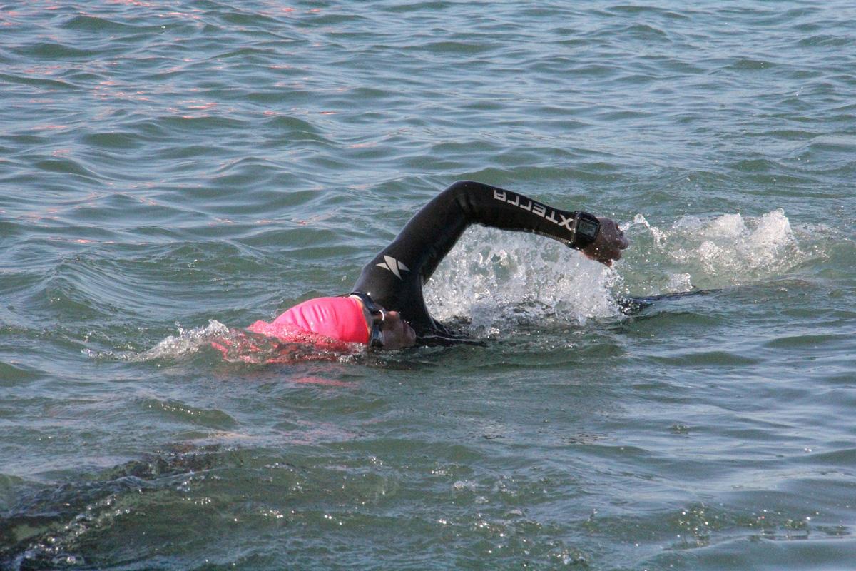 Triatleta si allena nuotando in acque libere