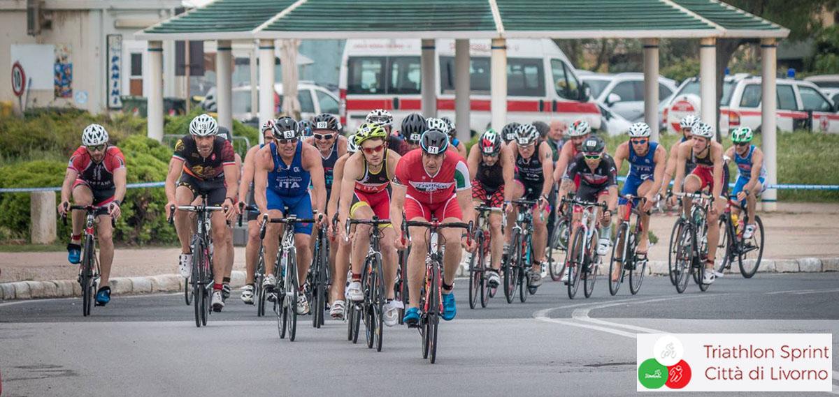 Un gruppo di ciclisti pedala su una strada del Triathlon Sprint città di Livorno
