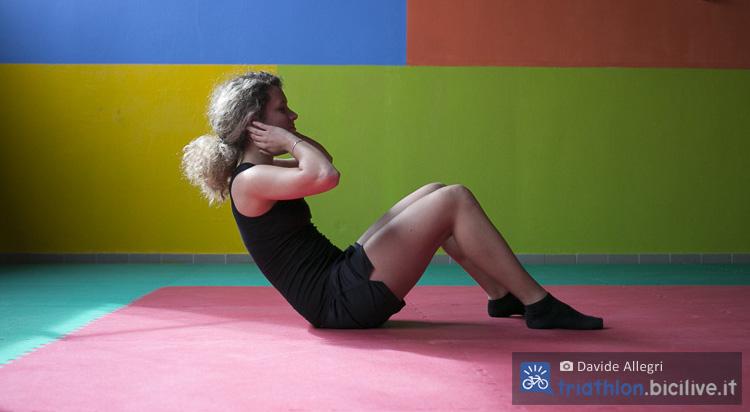 Atleta donna esegue un esercizio per gli addominali in palestra