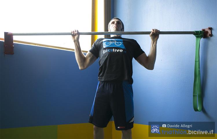 Atleta uomo si allena in palestra con un esercizio alla sbarra