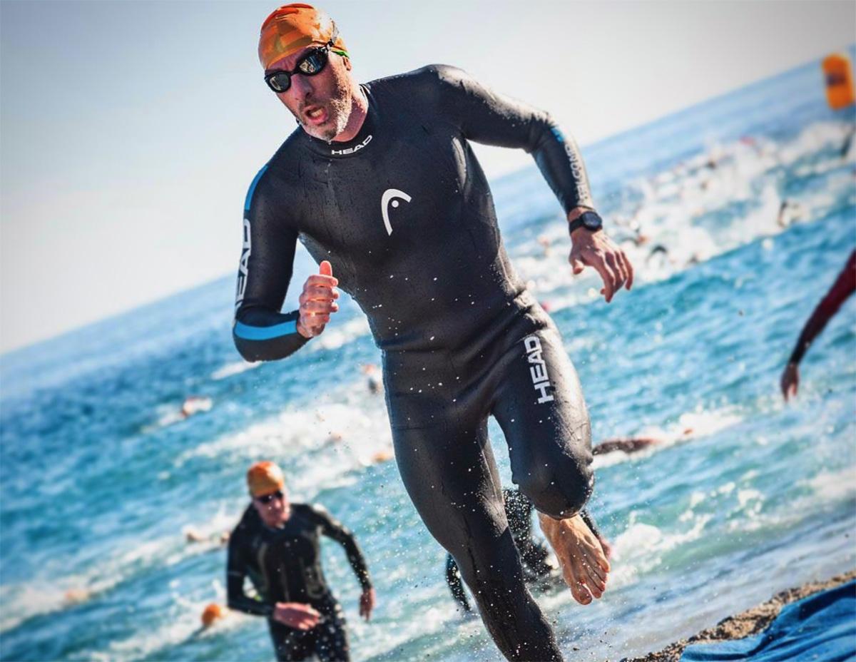 Un uomo esce dall'acqua correndo con al muta durante una gara di triathlon