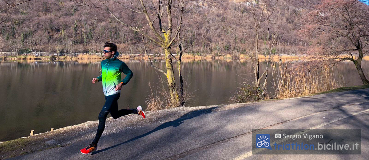 Un atleta si allena correndo attorno a un lago