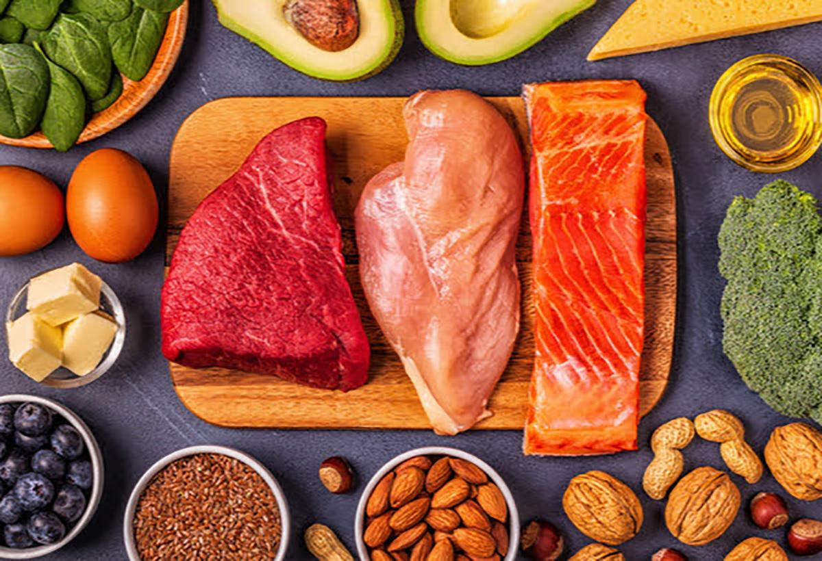 Diversi alimenti come pesce, carne, frutta e verdure sono posizionati su un piano